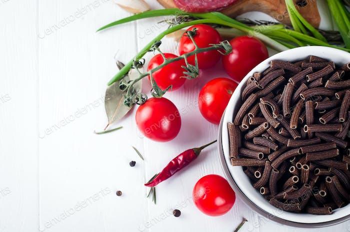 Trockene italienische Pasta Spiraline, rote Kirschtomaten, Wurst, Stillleben