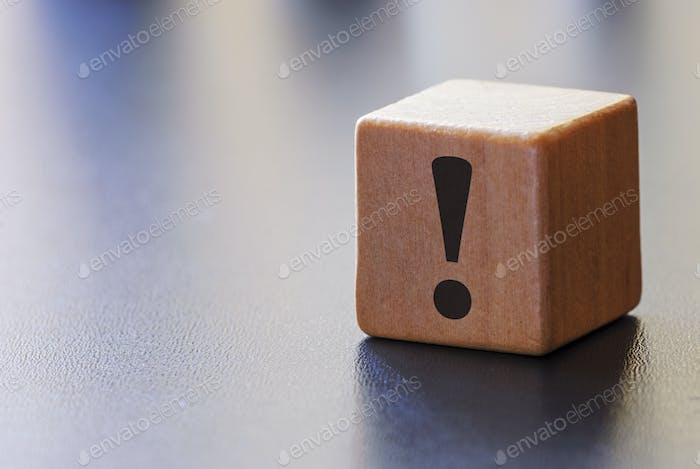 Señal de exclamación de advertencia en un bloque de madera