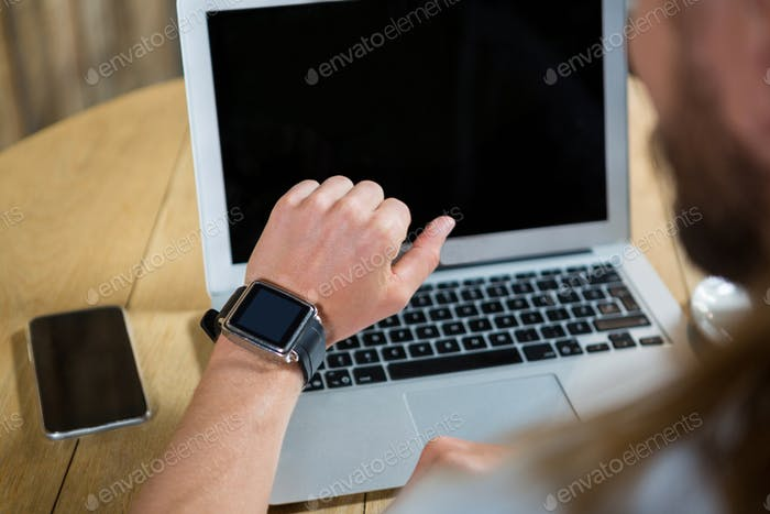 Man using smart watch with laptop and mobile phone on table in cafe