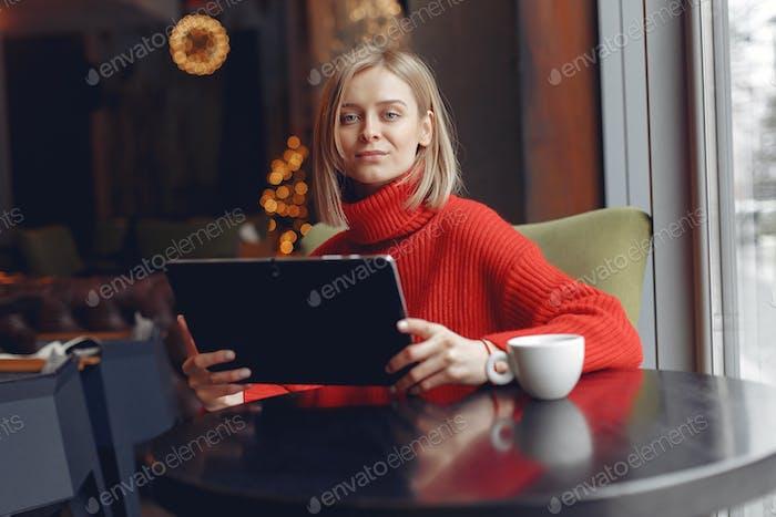 Geschäftsfrau in einem roten Pullover funktioniert