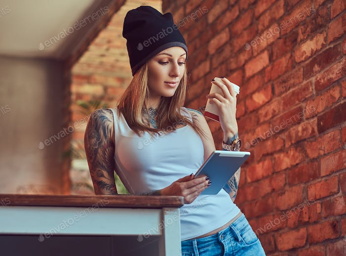 A stylish tattoed blonde female in t-shirt and jeans