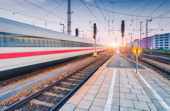 High speed train in motion on the railway station at sunset