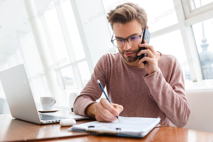 Image of man talking on cellphone and working with documents in cafe