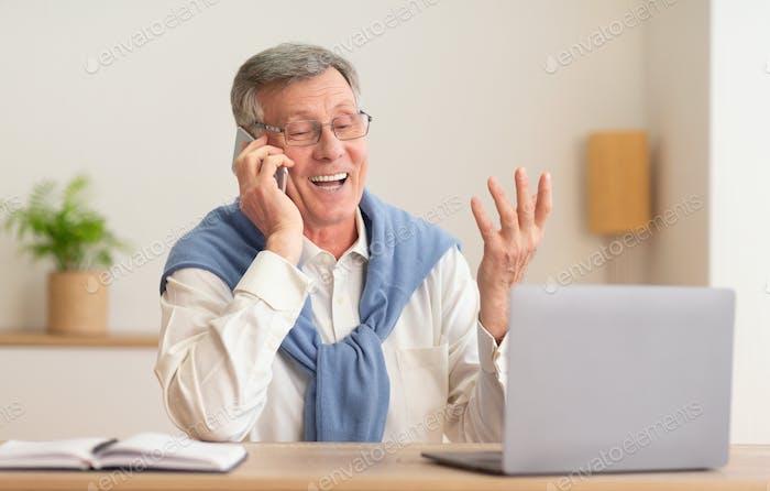 Gentleman Talking On Phone Working On Laptop At Workplace