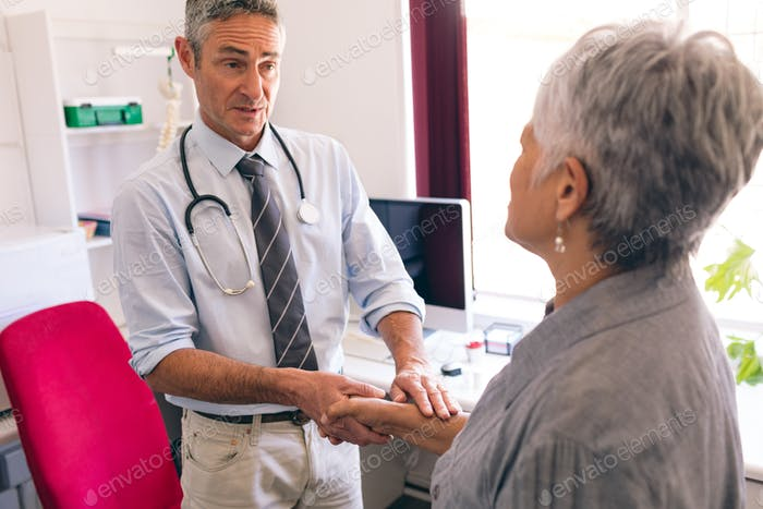 Male doctor interacting with senior female patient in clinic at retirement home