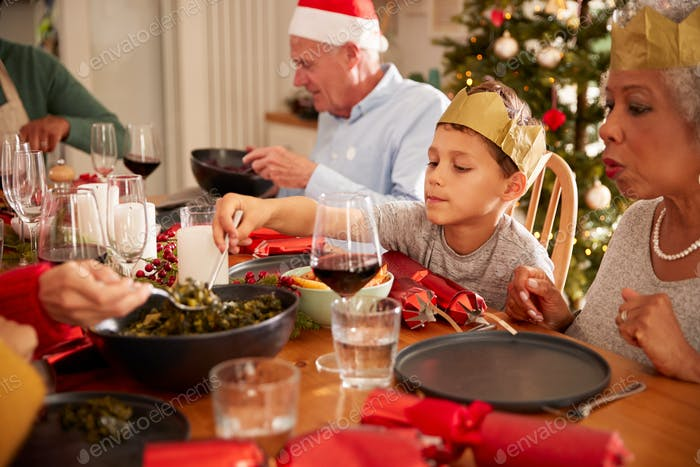 Multi-Generation Family Sitting At Dining Table Enjoying Christmas Meal At Home Together