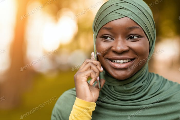 Mobile Communication. Black Islamic Woman In Headscarf Talking On Cellphone Outdoors