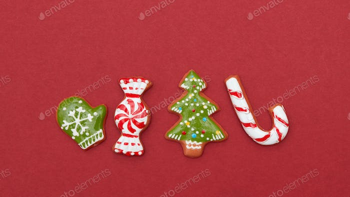 Four Christmas cookies on a red background