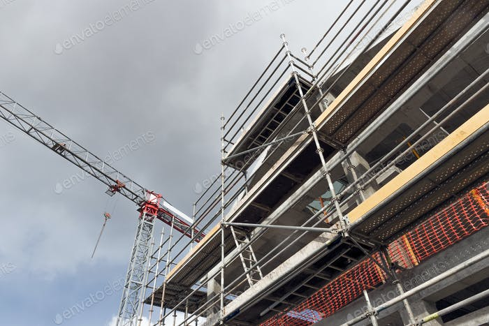Building construction site with crane and scaffolds