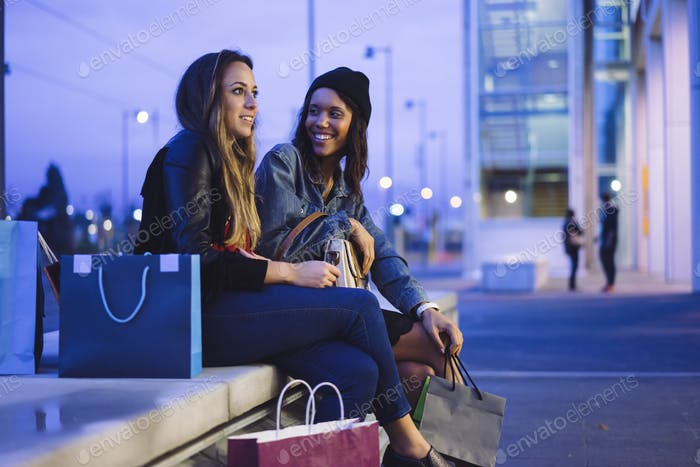 two female friends doing shopping in a city at night