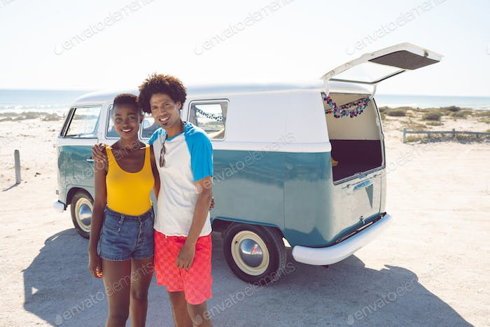 Front view of diverse couple looking at camera while standing near camper van at beach