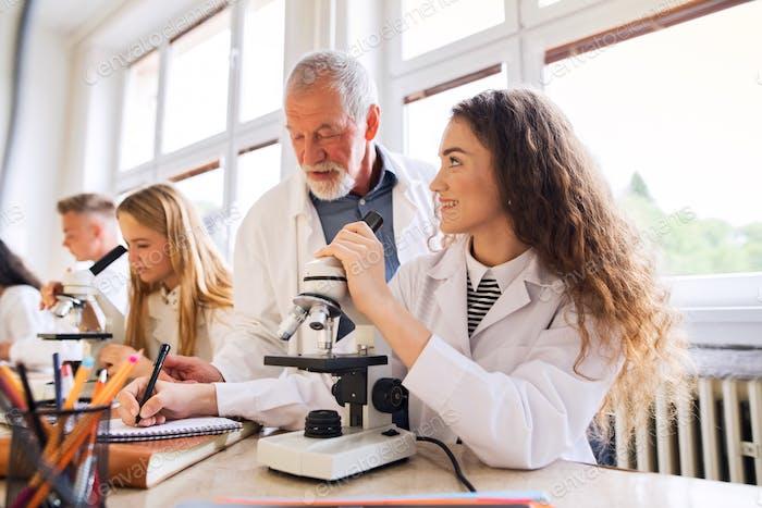 Senior teacher teaching biology to students in laboratory.