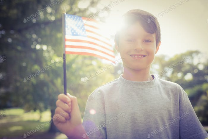 Little boy waving american flag on a sunny day