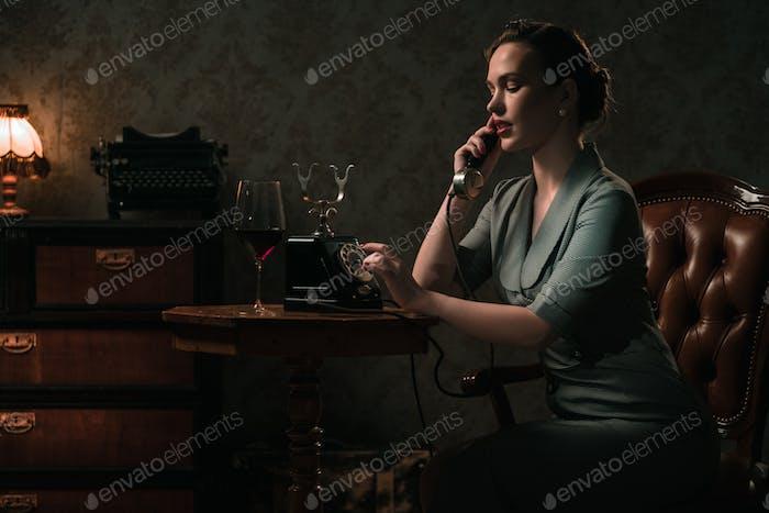 Hermosa Mujer joven en un teléfono en el interior Retro.
