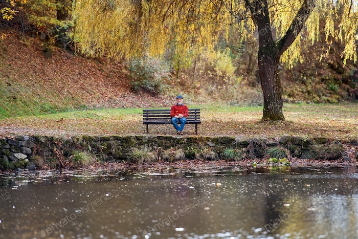 Lonely senior man sitting on bench by lake in nature, looking at camera