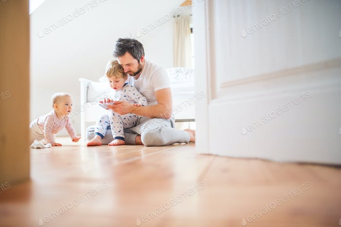 Father and toddler children with smartphone at home at bedtime.