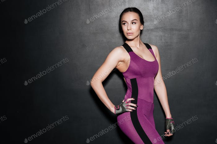 Strong sportswoman posing over grey background
