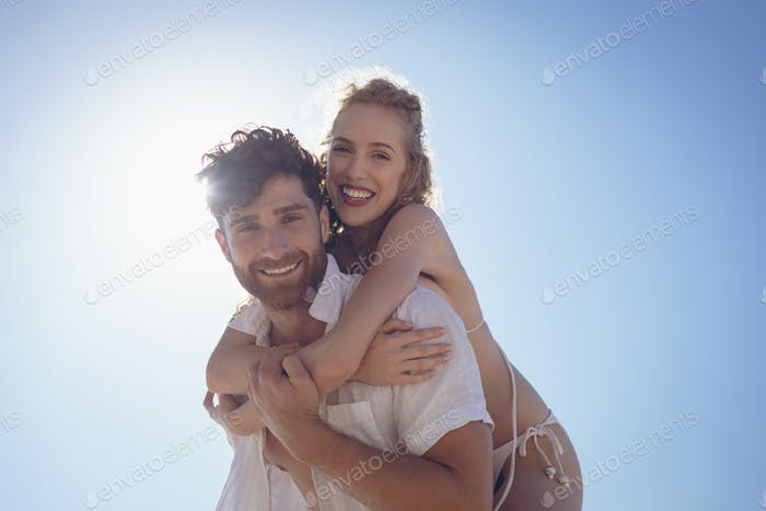 Young man carrying pretty woman piggyback at beach. They are smiling