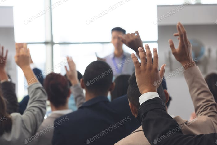 Rear view of diverse business people raising hands in a business seminar in office building
