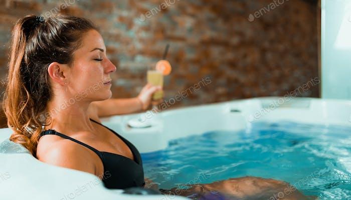 Beautiful Woman Enjoying Jacuzzi in Spa Center.