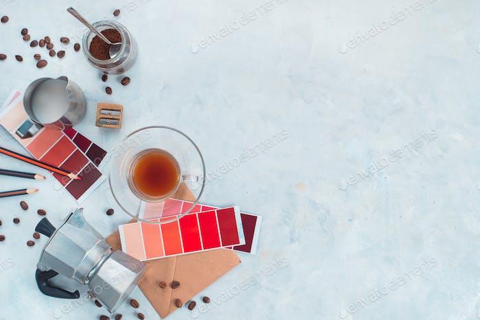 Farbdesign-Produktion. Künstlerarbeitsplatz von oben. Mokka Kaffeekanne, Farbmuster, Bleistifte