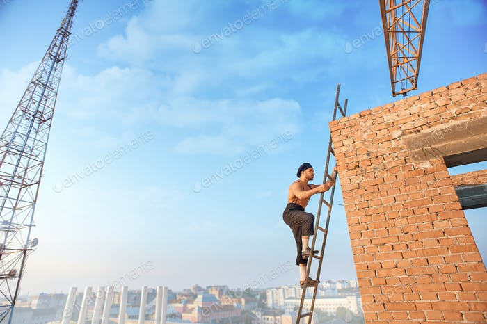 Builder with bare climb on ladder up