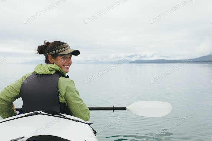 Woman sea kayaking turning to look behind her