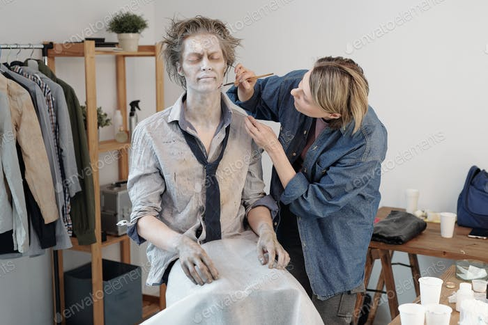 Blond visage artist with brush applying zombie makeup on face and neck of young businessman or actor