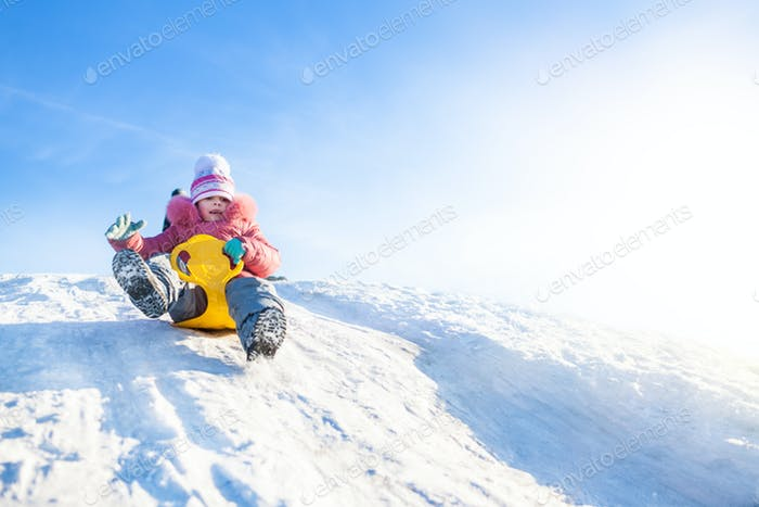 Happy small girl in winter clothing riding downhill