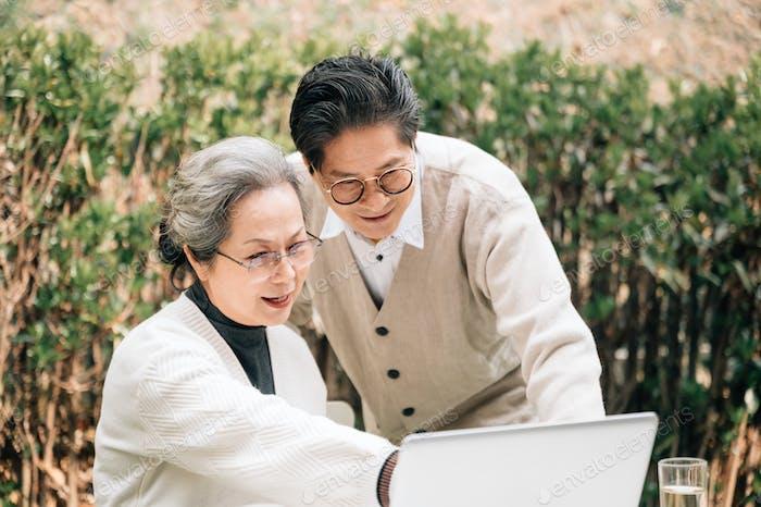 Senior-Paar mit Laptop im Hof