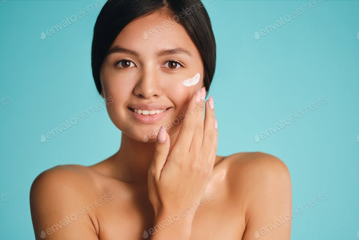 Pretty smiling Asian brunette girl applying cream on clean skin happily looking in camera
