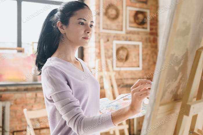 Beautiful Woman Painting Picture in Art Studio