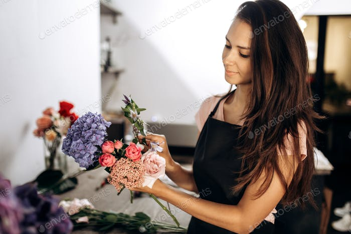 Florist collections a bouquet of fresh pink little roses, blue hydrangea and other flowers in the