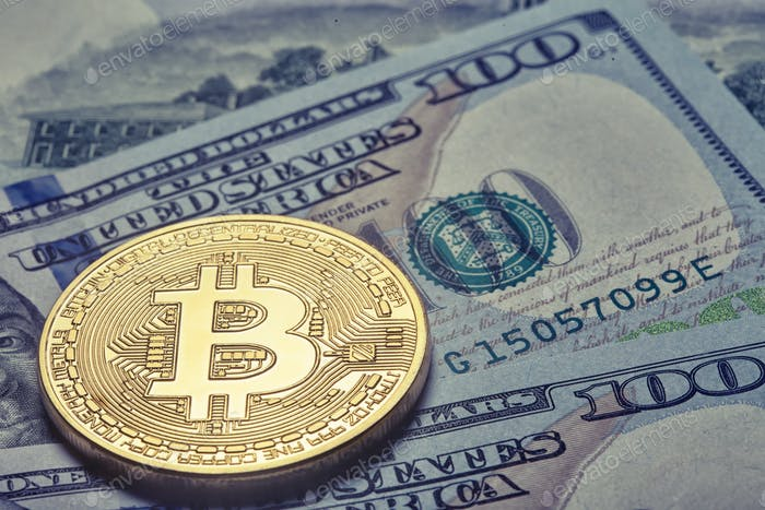 Golden shiny bitcoin on the background of one hundred dollar bil