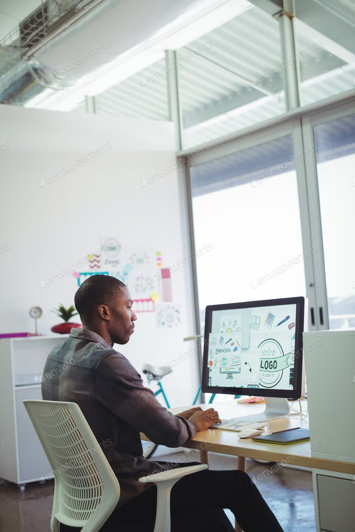 Serious businessman using computer in creative office