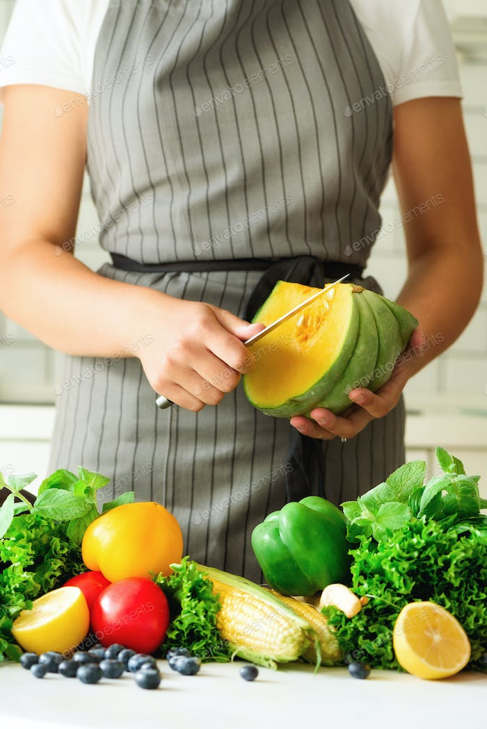 Woman peeling pumpking, vegetables, onion, tomatoes, corn, bell pepper, spinach, lettuce leaves