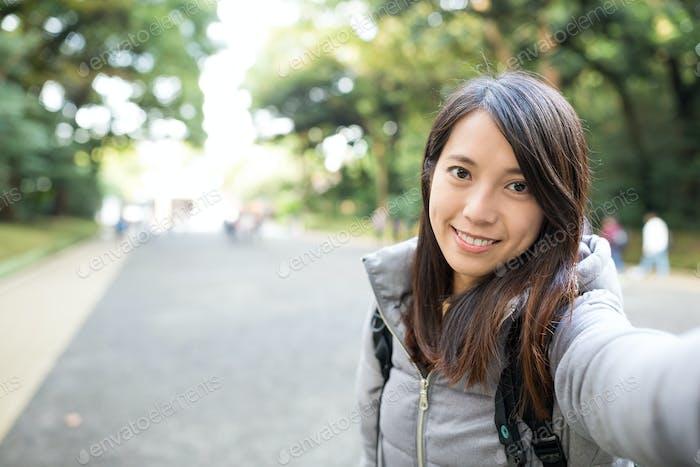 Frau hält Kamera für das Fotografieren von selbst