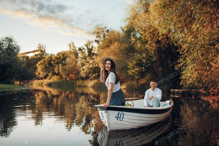 Pretty lady poses in boat on quiet lake