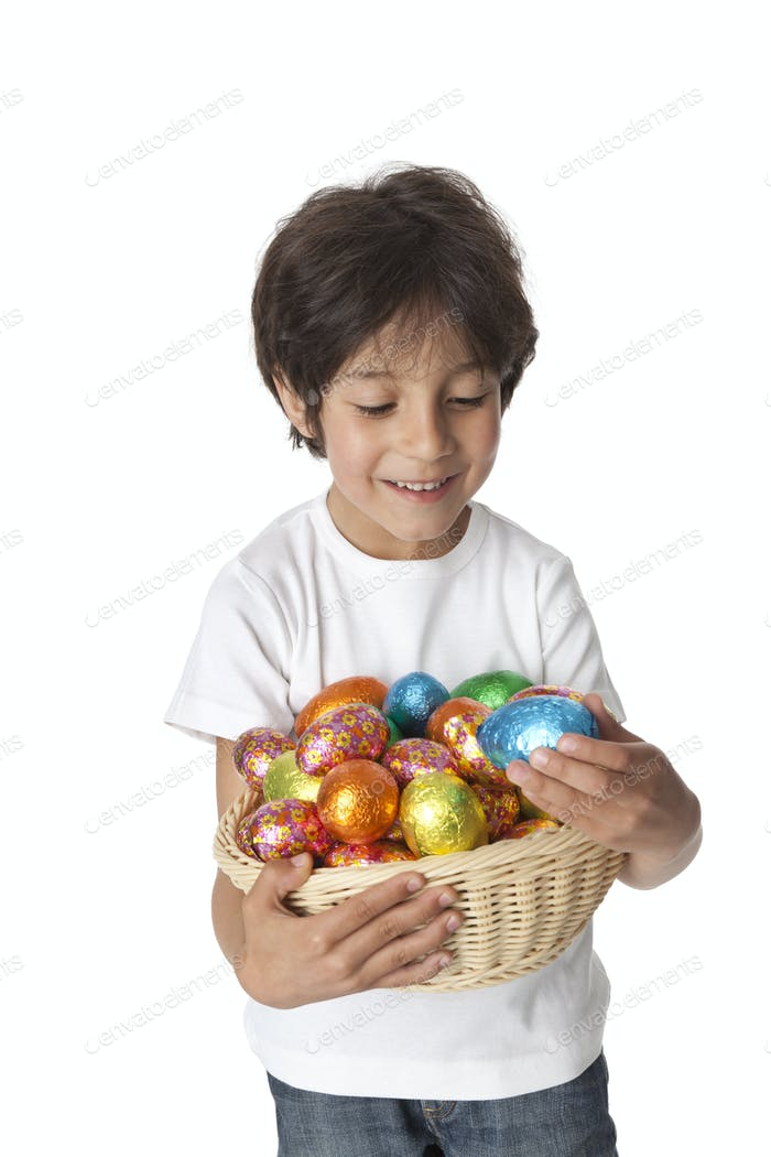 Little boy with a basket of chocolate Easter eggs