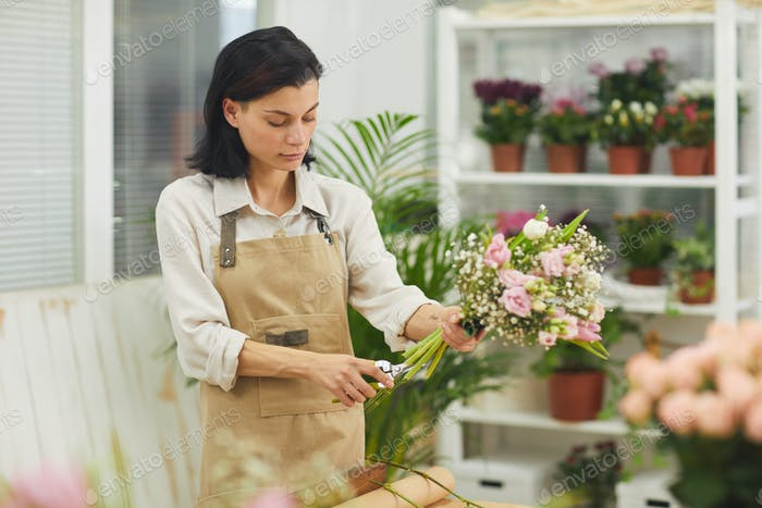 Young Woman Arranging Flowers in Shop
