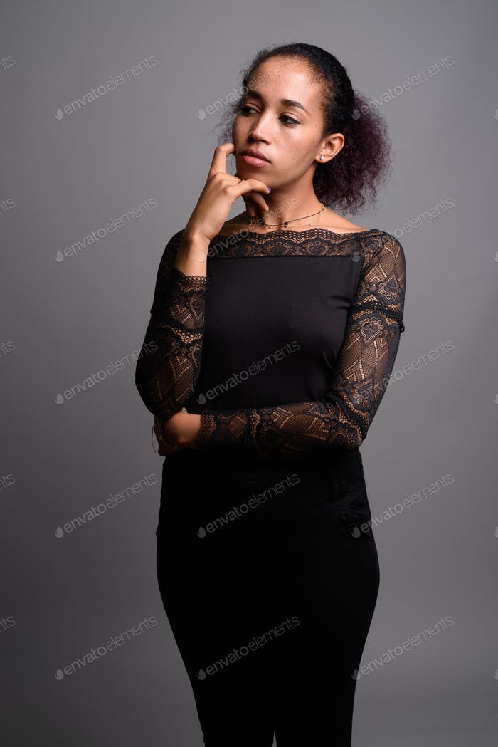 Young beautiful African woman against gray background