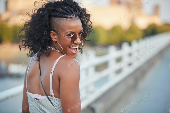 Trendy woman in striped camisole and sunglasses, turning