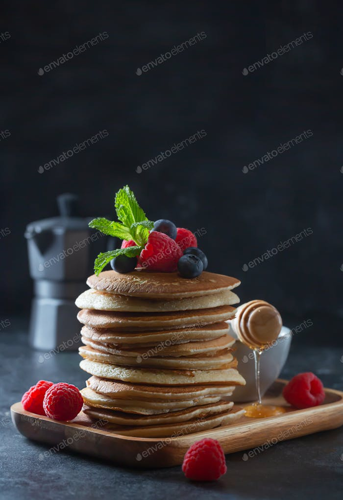 Pancakes with blueberries, raspberries, mint and honey for a breakfast