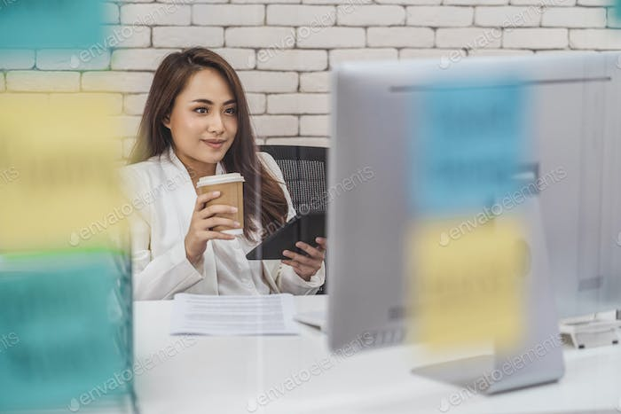 Asian Business woman holding paper coffee cup and mobile phone when working