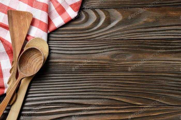 Rote, karierte Serviette und Utencils aus Holz auf braunem Küchentisch mit Kopierraum. Ansicht von oben