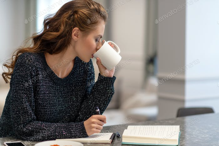 Young woman working at home using notepad in kitchen.