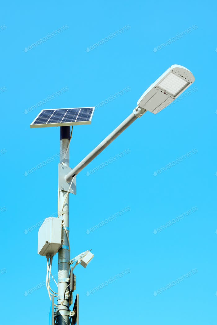 Solar panel powered street light lamp on blue sky background