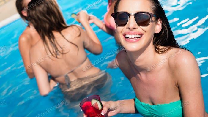 Woman enjoying cocktail at pool