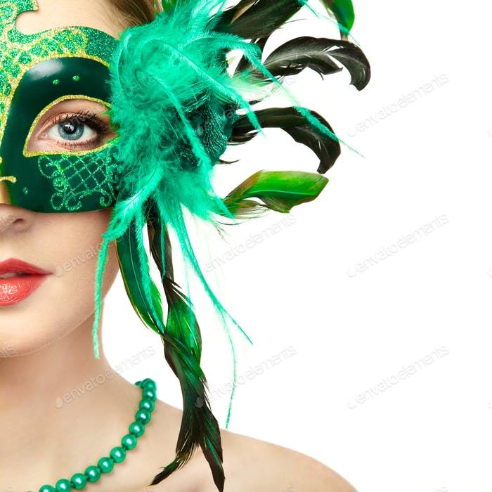 Beautiful young woman in mysterious green Venetian mask