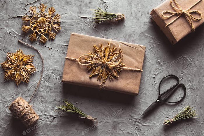 Creative hobby. Man's hands wrap christmas holiday handmade present in craft paper with twine